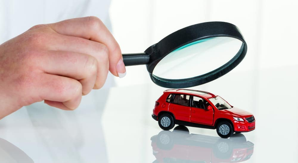 032c93978bf964 A hand holding a magnifying glass over a red toy car
