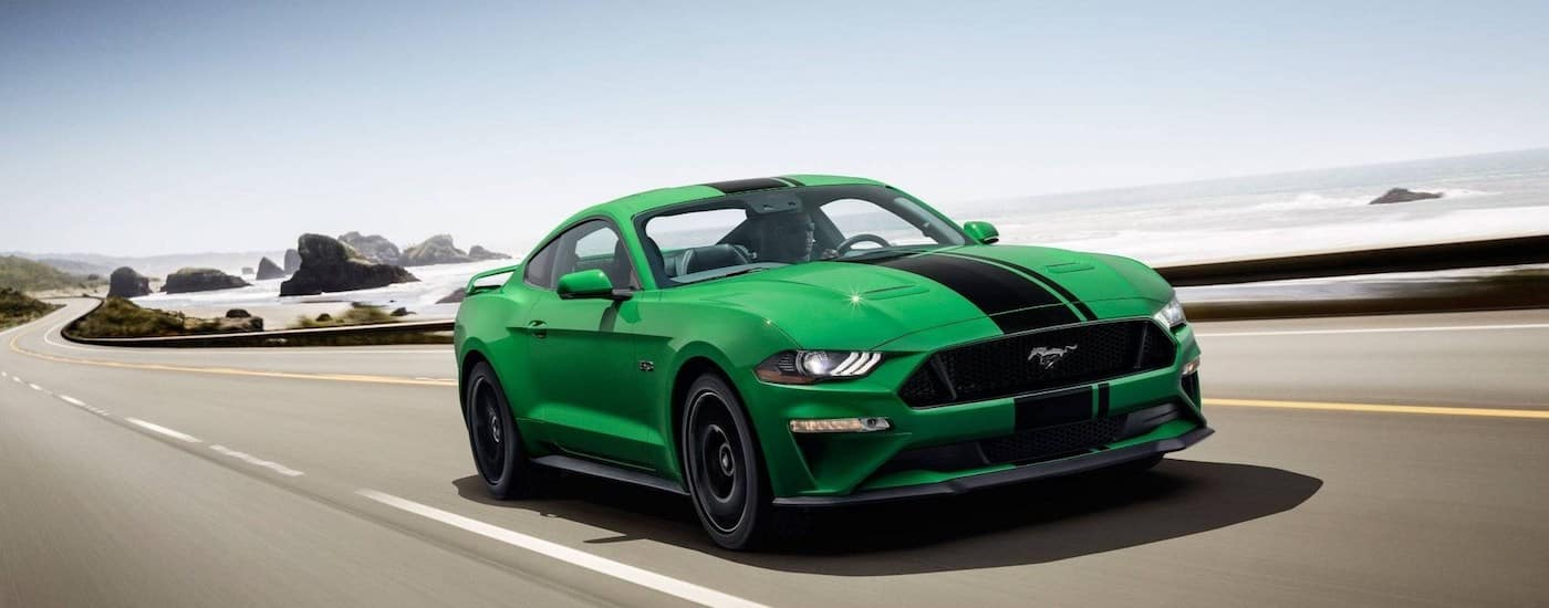 A bright green 2019 Ford Mustang speeds down a empty highway