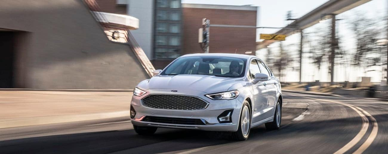 A clean white 2019 2019 Ford Fusion speeds through a corner on a local Cincinnati highway