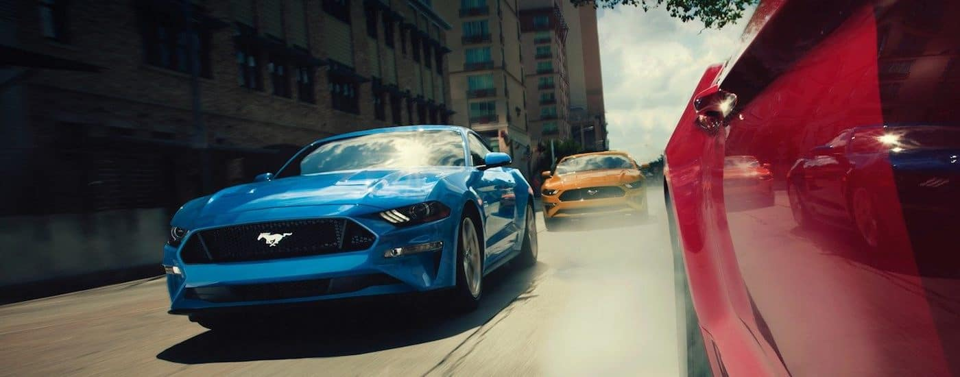 Red, blue, and yellow 2019 Ford Mustangs race down a street