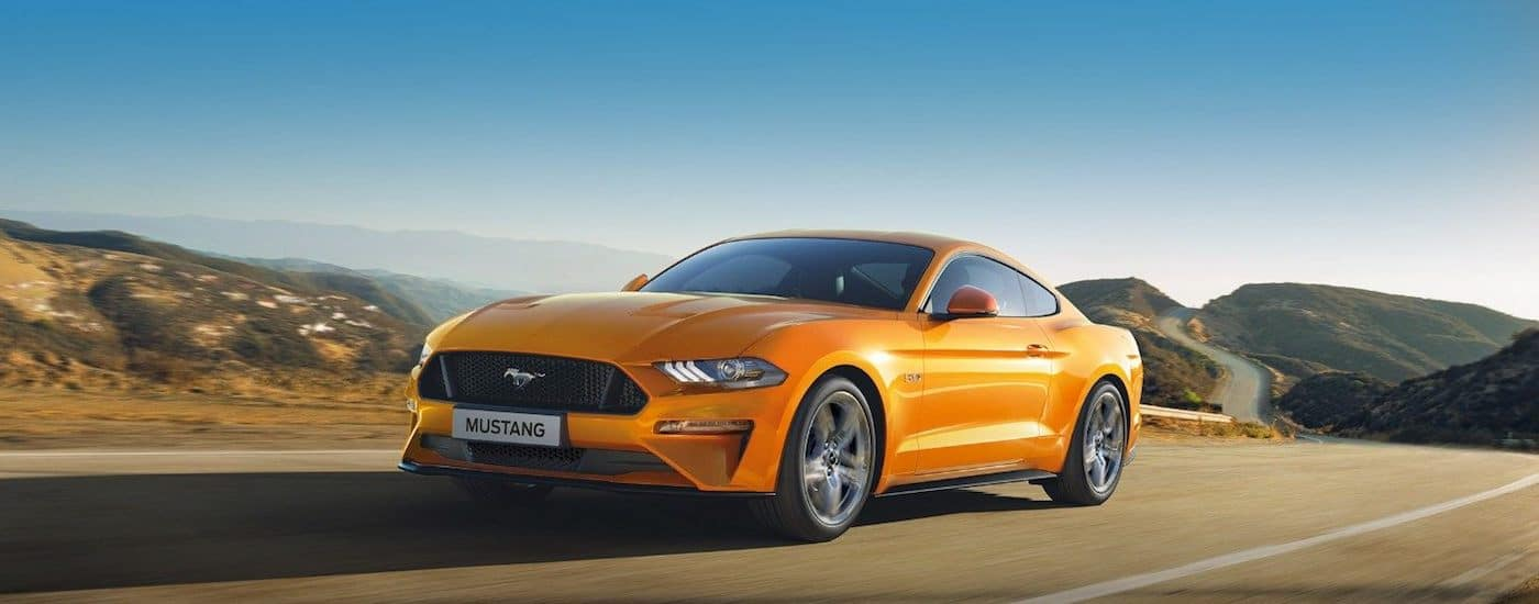 A bright yellow 2019 Ford Mustang takes a lap on a race track
