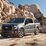 A gray 2015 Ford F150 in front of a rock pile