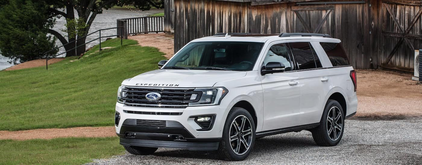 White 2019 Ford Expedition Limited in front of a barn and lake
