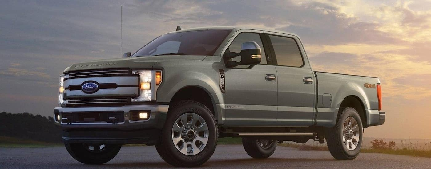 A gray 2019 Ford F-250 at the ocean at sunset