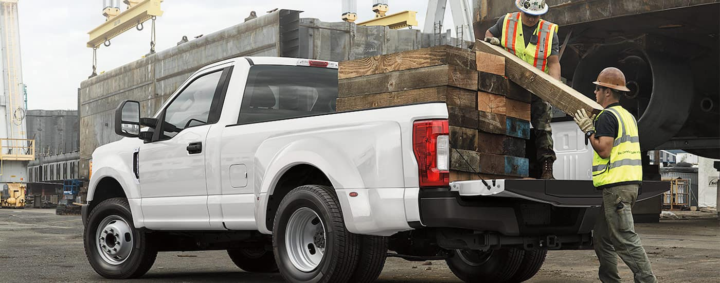 Two men loading lumber into a white 2019 Ford F-250