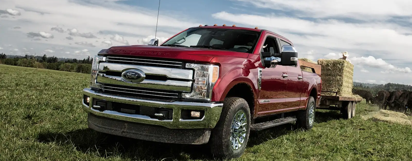 A red 2019 Ford F250 towing hay