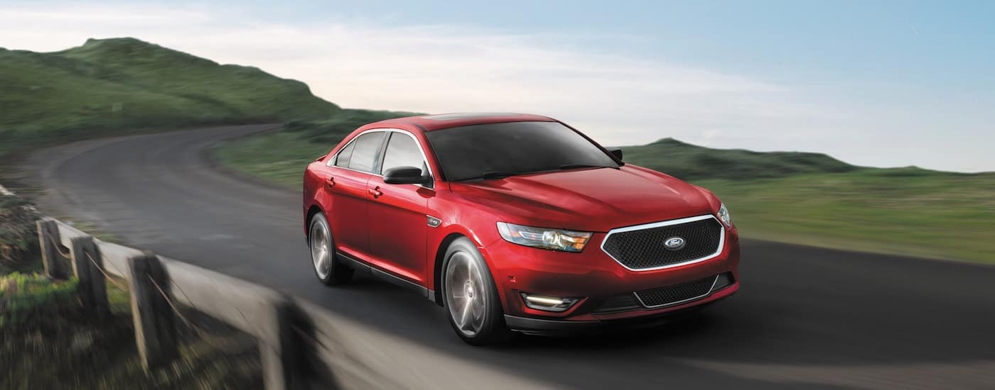 Red 2019 Ford Taurus driving in mountain range