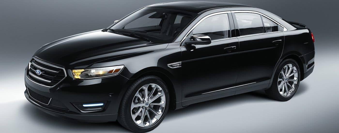 A Black 2019 Ford Taurus on a gray background