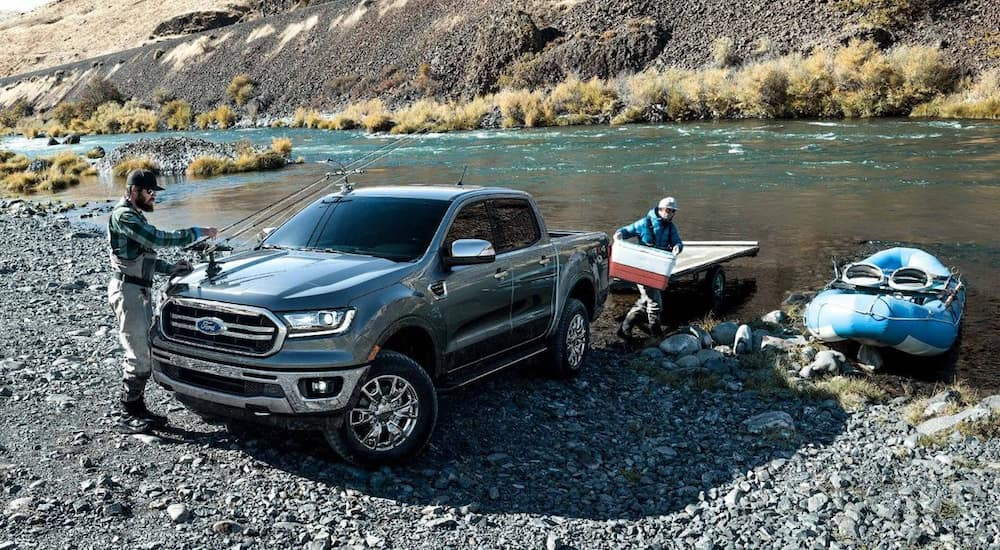 A blue 2019 Ford Ranger pulls a boat and trailer out of a river