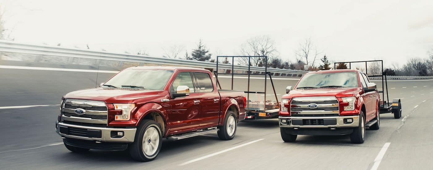 Two red used Ford F-150 tow trailers side by side