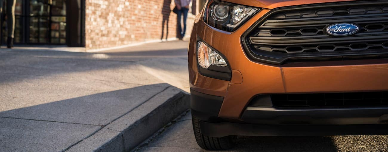 An orange 2019 Ford EcoSport sits confidently on a city street knowing that it's won the comparison of 2019 Ford EcoSport vs 2019 Chevy Trax