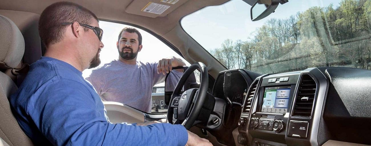 2 men talk while in the interior if a 2019 Ford F150
