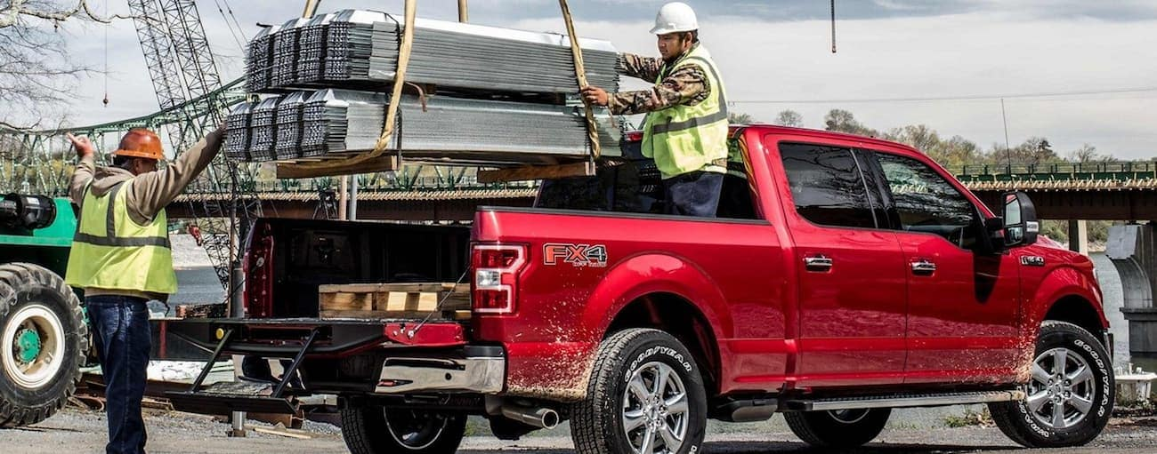 A red 2019 Ford F150 getting loaded with heavy cargo