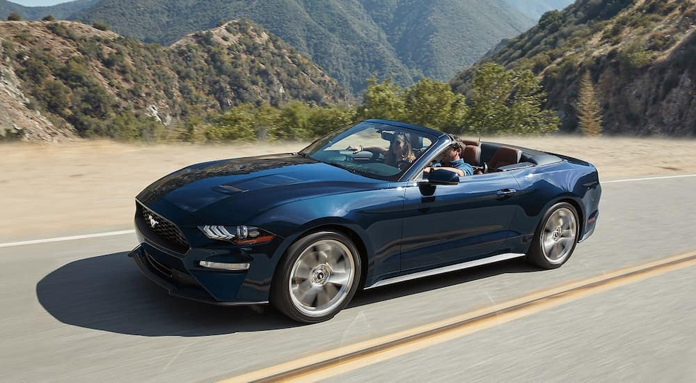 A blue 2019 Ford Mustang convertible cruises a mountain road with the top down