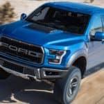 A blue 2019 Ford F150 Raptor cruising in the desert