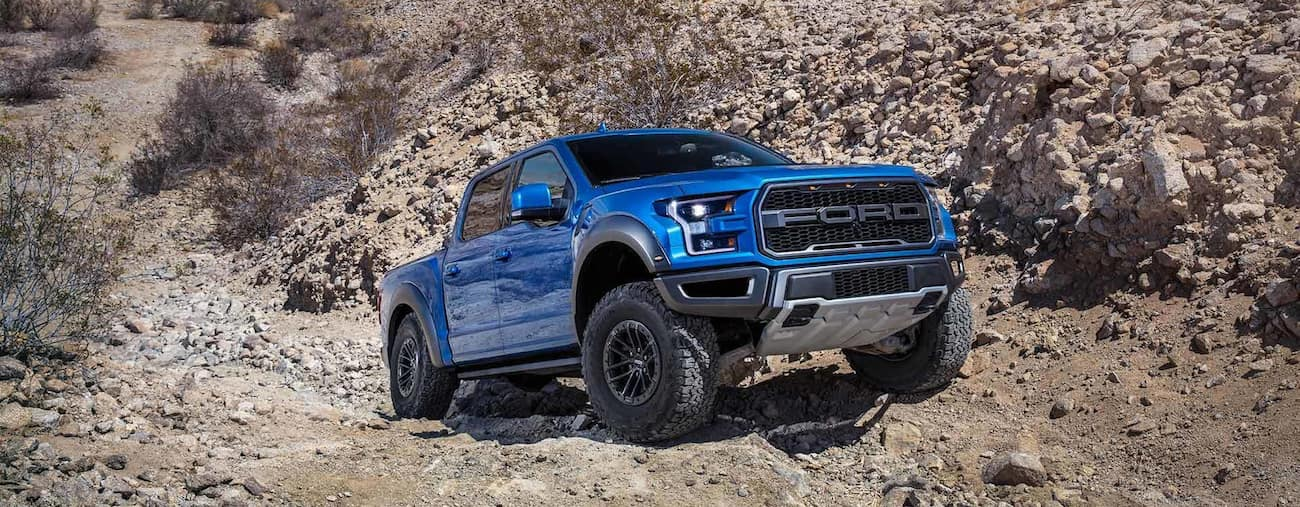 A blue Ford F150 Raptor climbing over rocks
