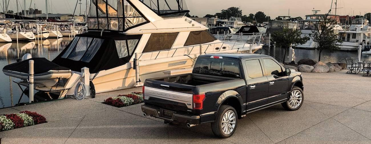 A black 2019 Ford F-150 parked next to a large yacht