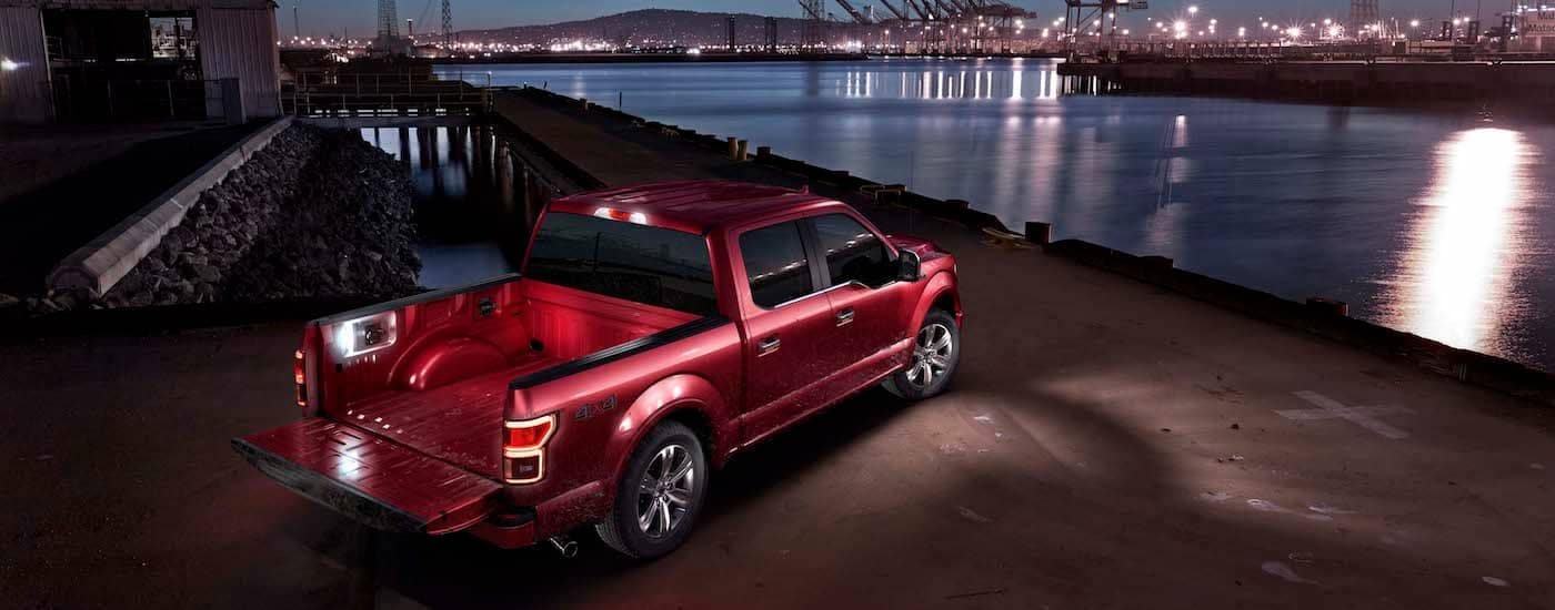 A deep red 2019 Ford F-150 at a shipping dock by a harbor at dusk