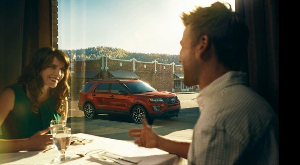 A couple enjoys dinner with their red 2016 used Ford Explorer out the window