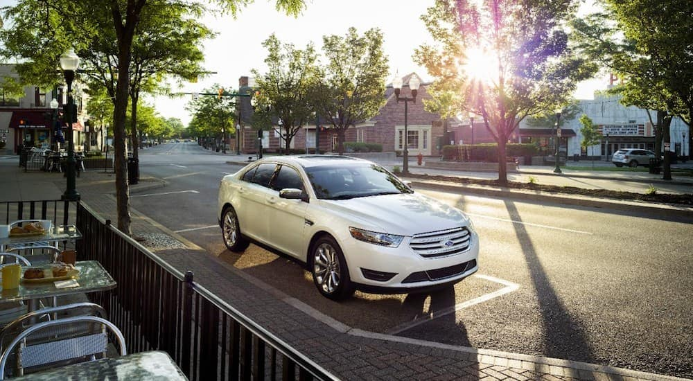 A white 2016 used Ford Taurus parked outside a cafe at dusk