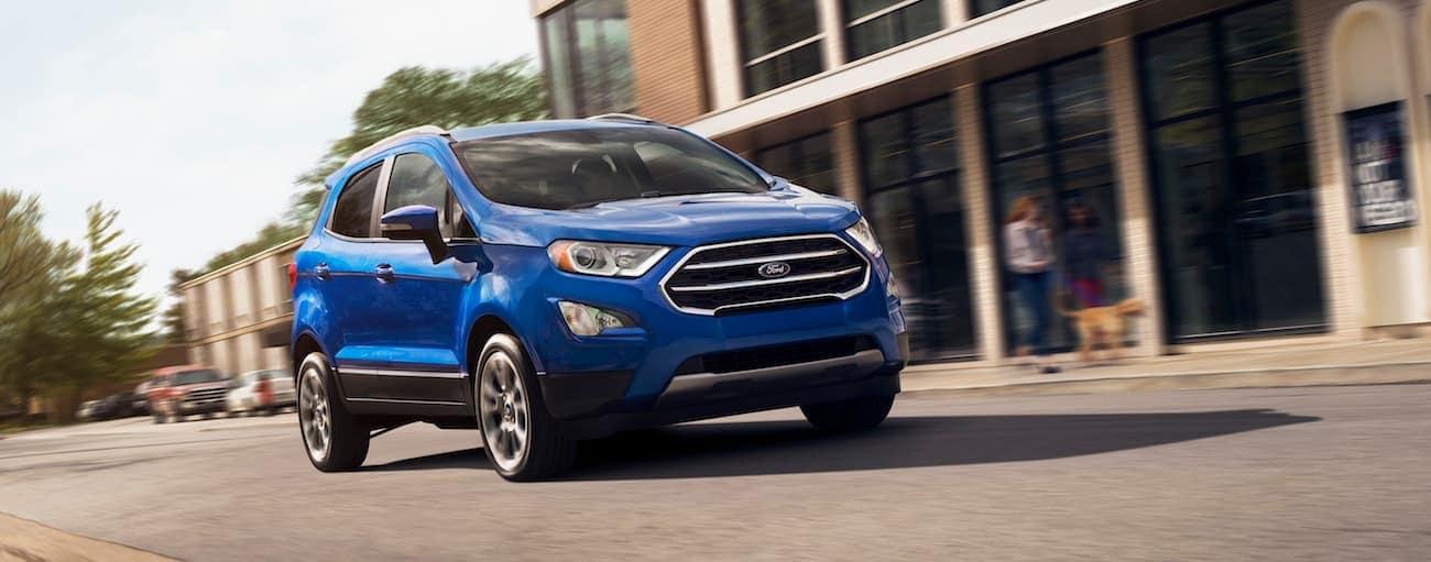 A blue 2019 Ford EcoSport drives down a city street