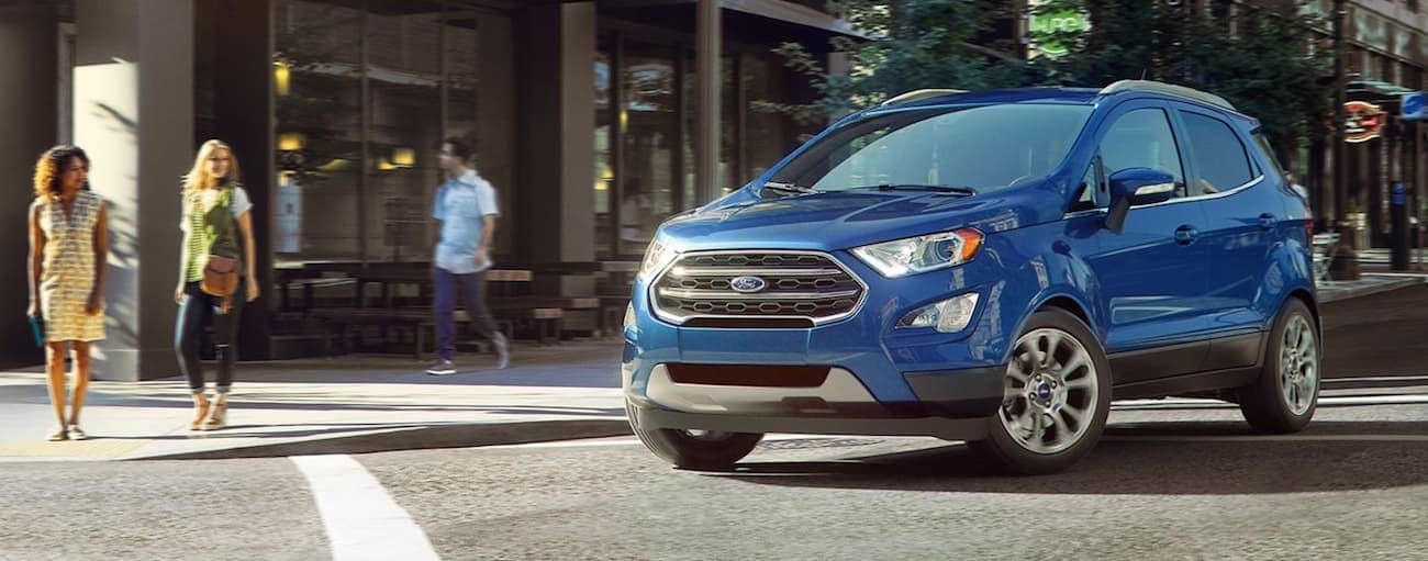A blue 2019 Ford EcoSport drives through a city, turning heads as it goes