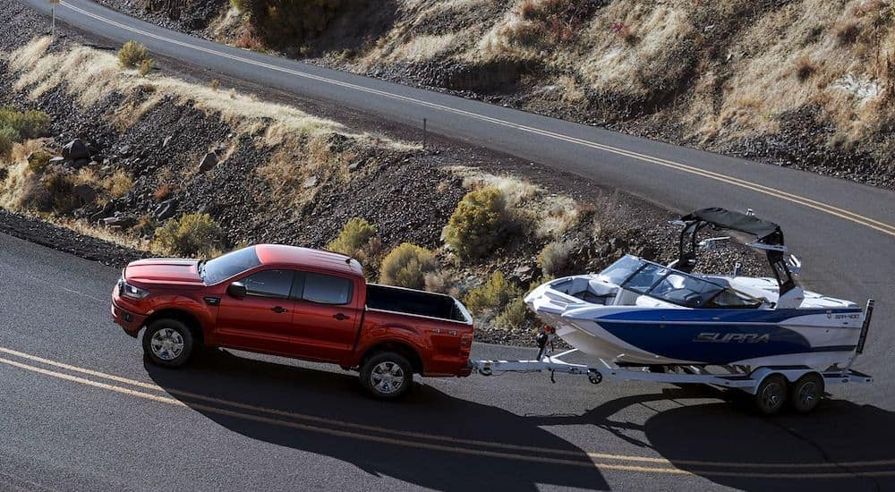 A red 2019 Ford Ranger tows a boat up a mountain road