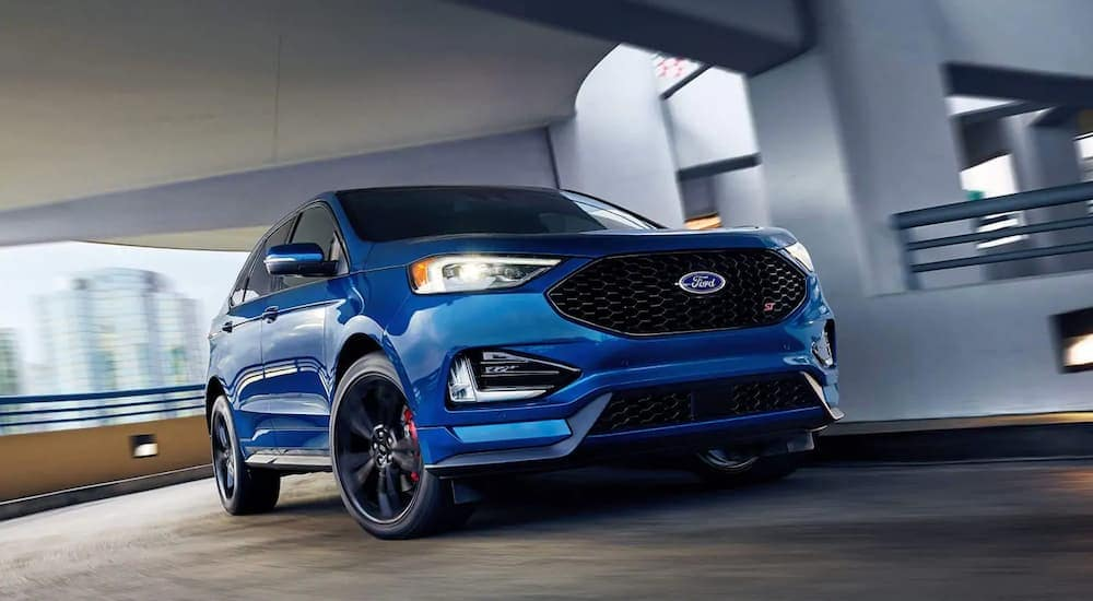 A blue 2019 Ford Edge is driving through a parking garage.