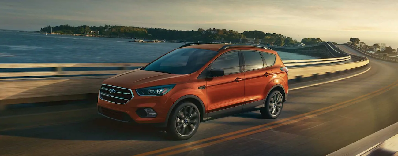 An orange 2019 Ford Escape is driving along a corner with a bay behind it.
