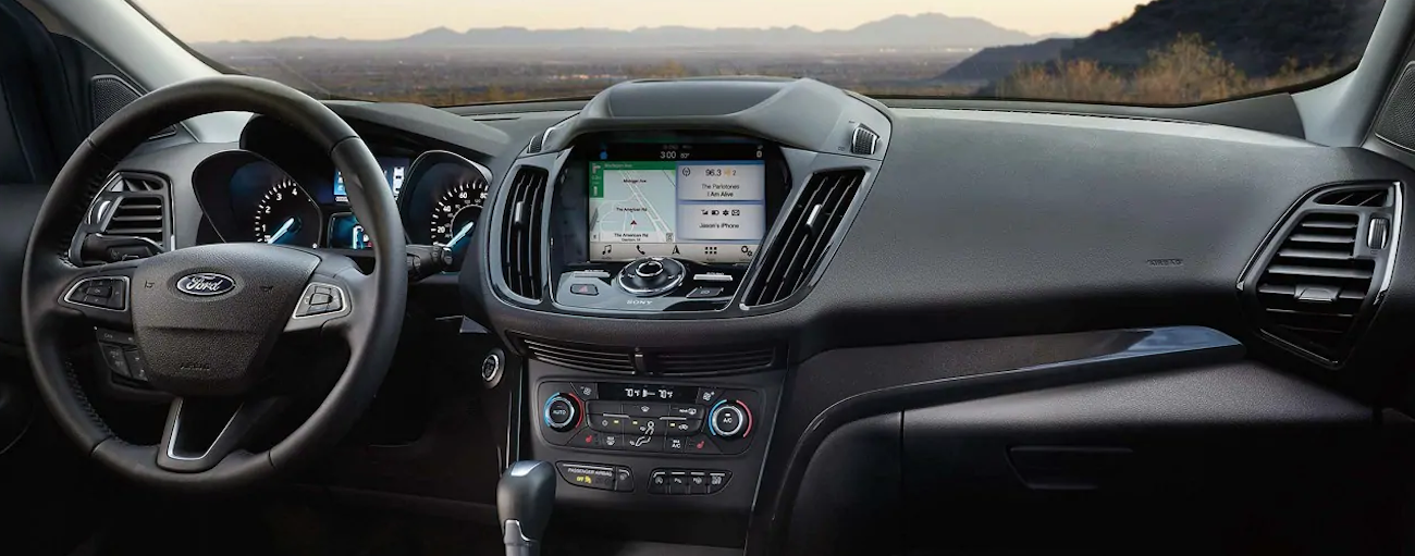 The black interior and entertainment features of the 2019 Ford Escape are shown. When comparing the 2019 Ford Escape vs 2019 Honda CR-V, the Escape has better options.