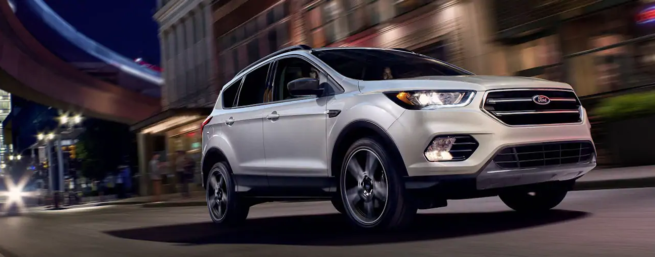 A white 2019 Ford Escape is taking a corner at night in the city.