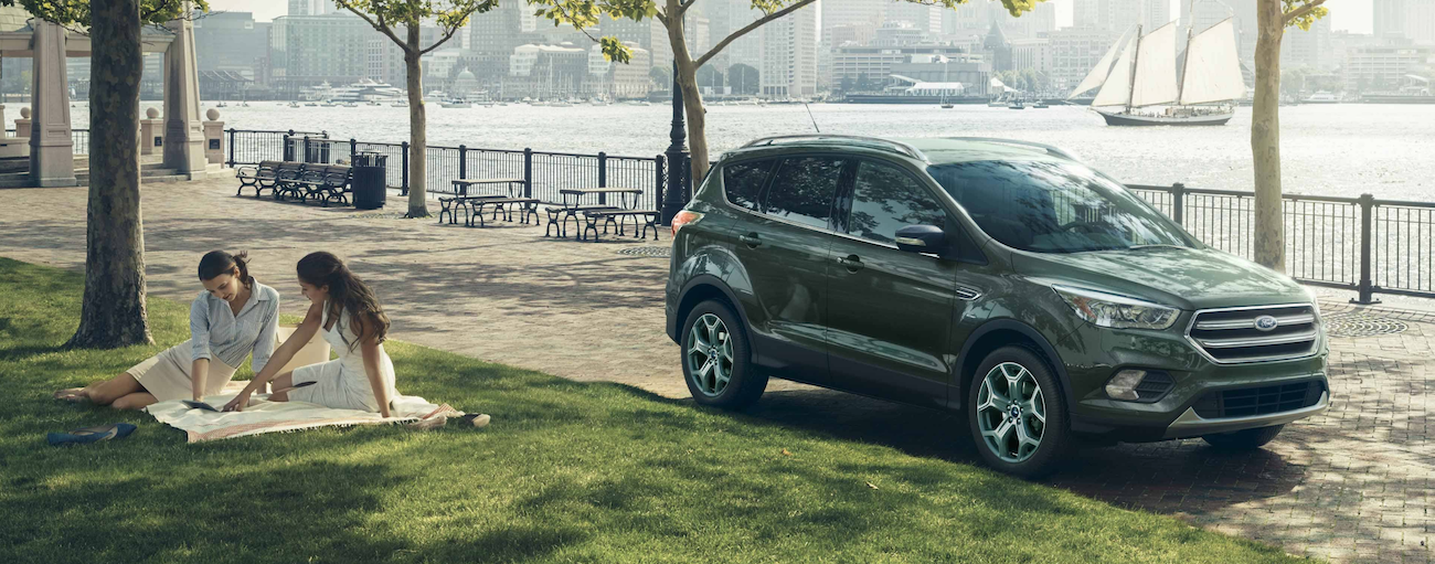 A green 2019 Ford Escape is parked next to a city park where two women are sitting on a blanket and a sailboat is in the water behind it.