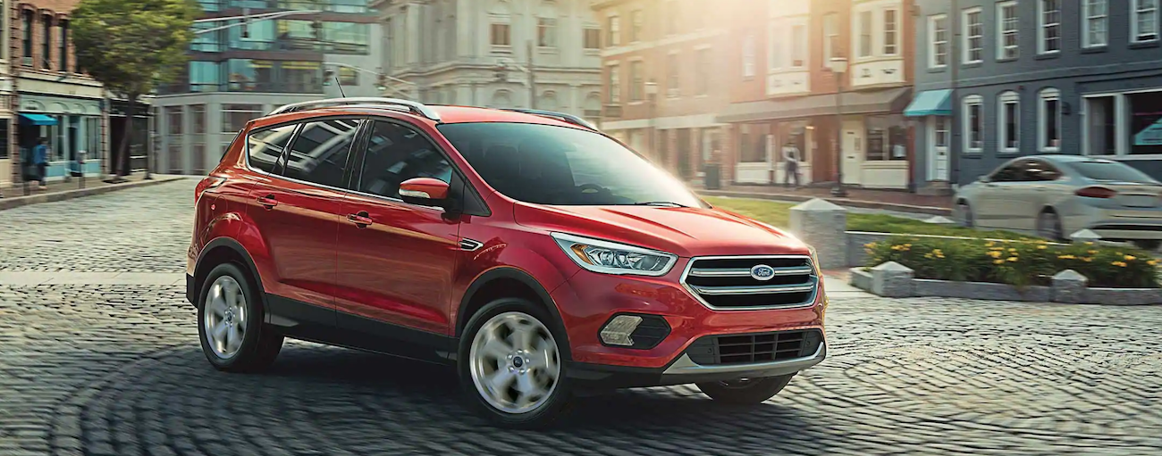 A red 2019 Ford Escape is turning a corner on a cobblestone road.