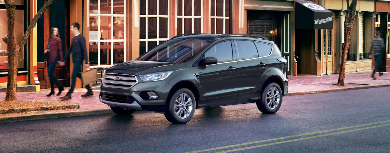 A dark 2019 Ford Escape is parked outside city buildings on a rainy day.