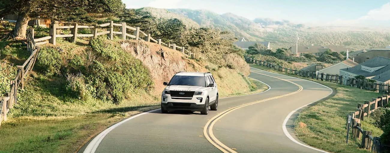 A white 2019 Ford Explorer is driving on a windy road up hill. Check out safety when comparing the 2019 Ford Explorer vs 2019 Honda Pilot in Cincinnati, OH.