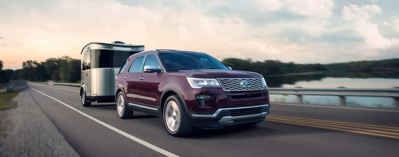 A burgundy 2019 Ford Explorer is towing a small trailer outside of Cincinnati, OH. Check out performance when comparing the 2019 Ford Explorer vs 2019 Toyota Highlander.