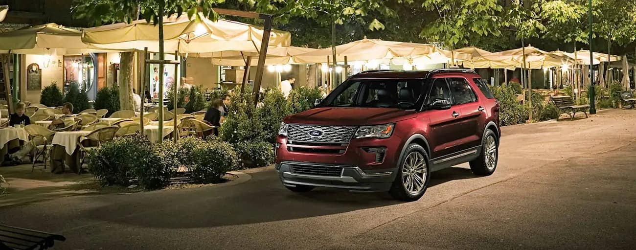 A red 2019 Ford Escape Platinum edition is parked outside a restaurant at night near Cincinnati, OH. Check out exterior styling when comparing the 2019 Ford Explorer vs 2019 Toyota Highlander.