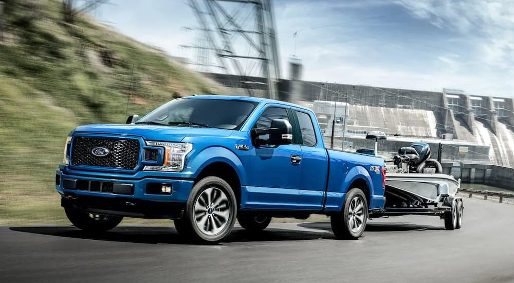 A blue 2019 Ford F-150 is towing a boat.
