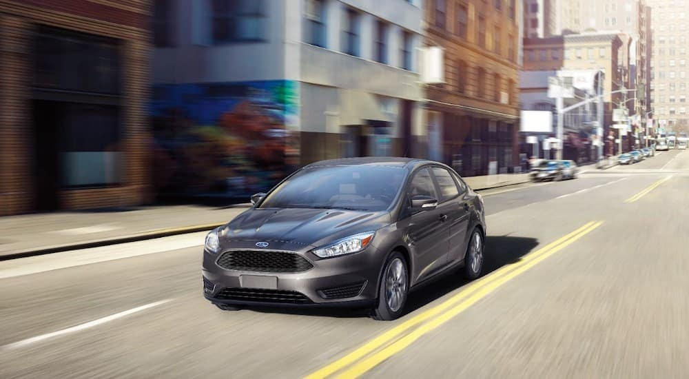A grey 2016 Ford Focus, purchased as a Ford Certified Pre Owned vehicle in Cincinnati, OH, is driving downtown.