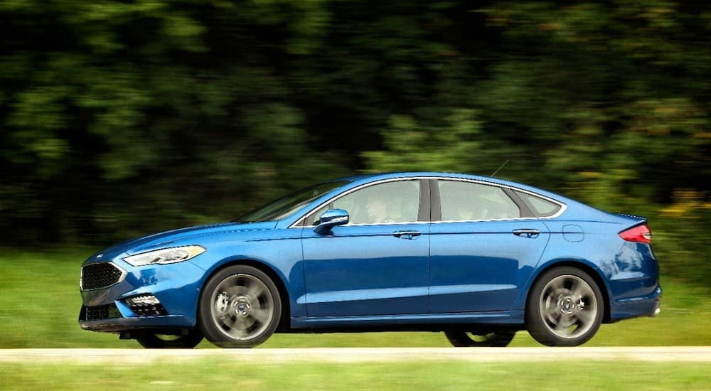 A blue 2017 Ford Fusion is driving in front of greenery and was purchased as a Ford Certified Pre Owned Vehicle in Cincinnati, OH.