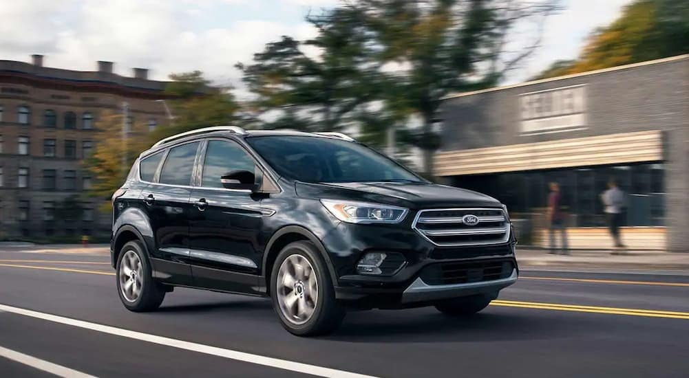 A black 2019 Escape, one of the Ford SUVs available in Cincinnati, OH, is driving in front of a shop.