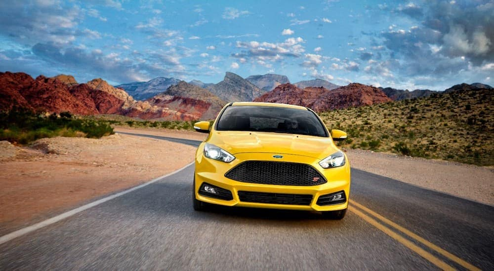 A yellow 2017 Ford Focus is driving on a road through the desert. The Focus is an option for used cars in Cincinnati.