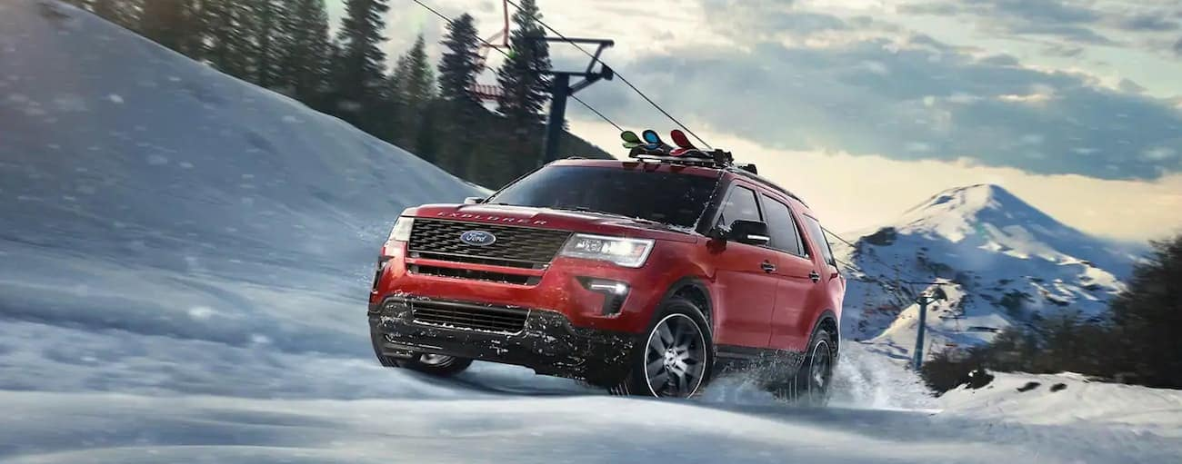 A red 2019 Ford Explorer is driving uphill in the snow with skis on the roof rack. Check out performance when comparing the 2019 Ford Explorer vs 2019 Chevy Traverse in Cincinnati, OH.