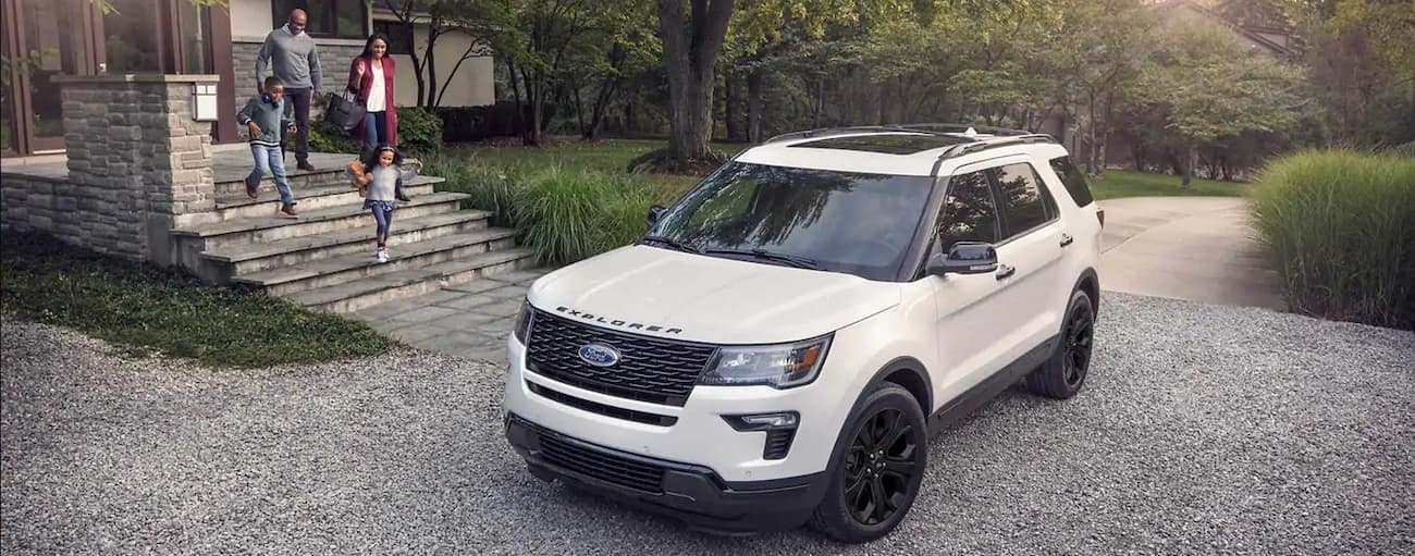 A white 2019 Ford Explorer with black trim is parked on a gravel driveway with a family walking towards it outside Cincinnati, OH. Check out safety when comparing the 2019 Ford Explorer vs 2019 GMC Acadia.