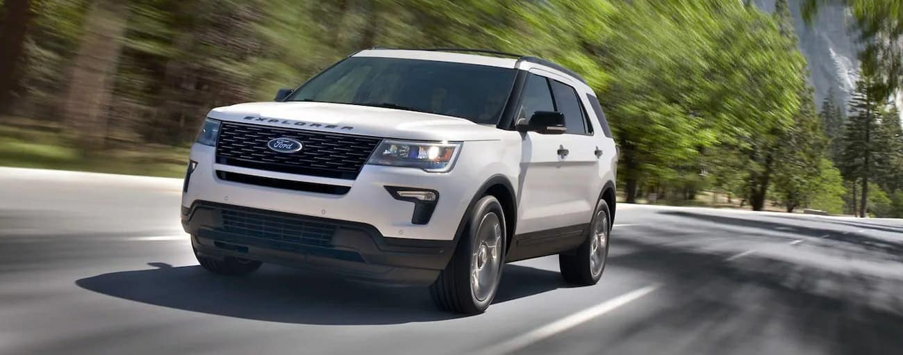 A white 2019 Ford Explorer is driving along a tree lined road outside Cincinnati, OH. Check out performance when comparing the 2019 Ford Explorer vs 2019 GMC Acadia.