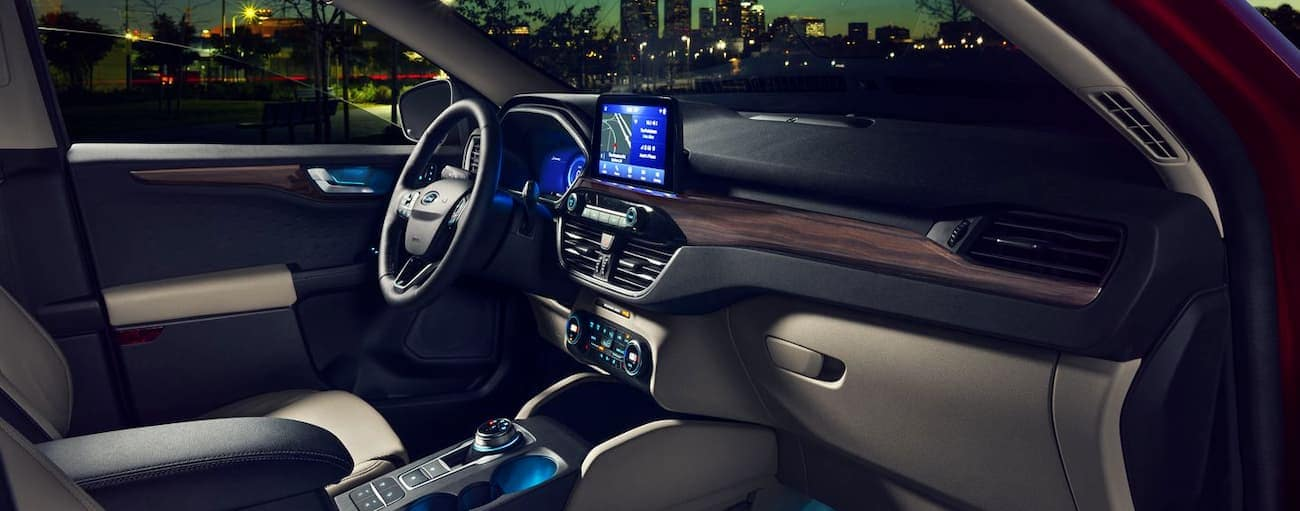 The front tan and black interior of the 2020 Ford Escape is shown with an infotainment system.
