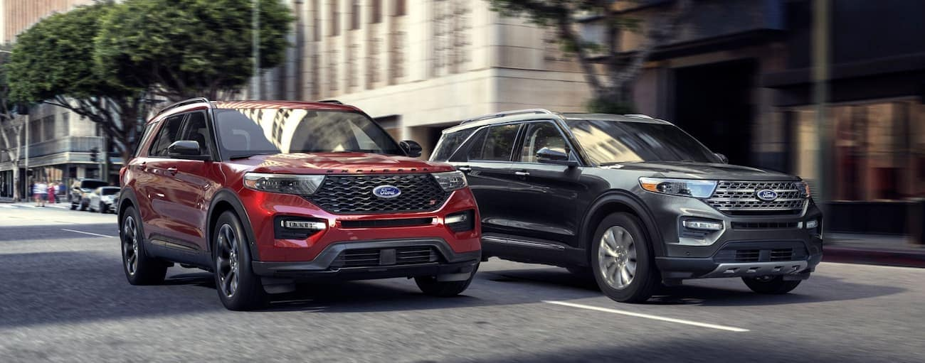 A grey and a red 2020 Ford Explorer are driving down a Cincinnati, OH city street side by side.