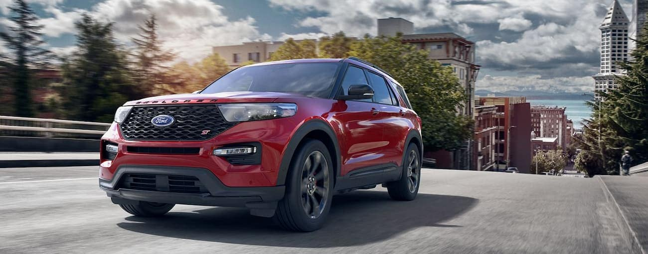 A red 2020 Ford Explorer ST is driving away from a city bay.