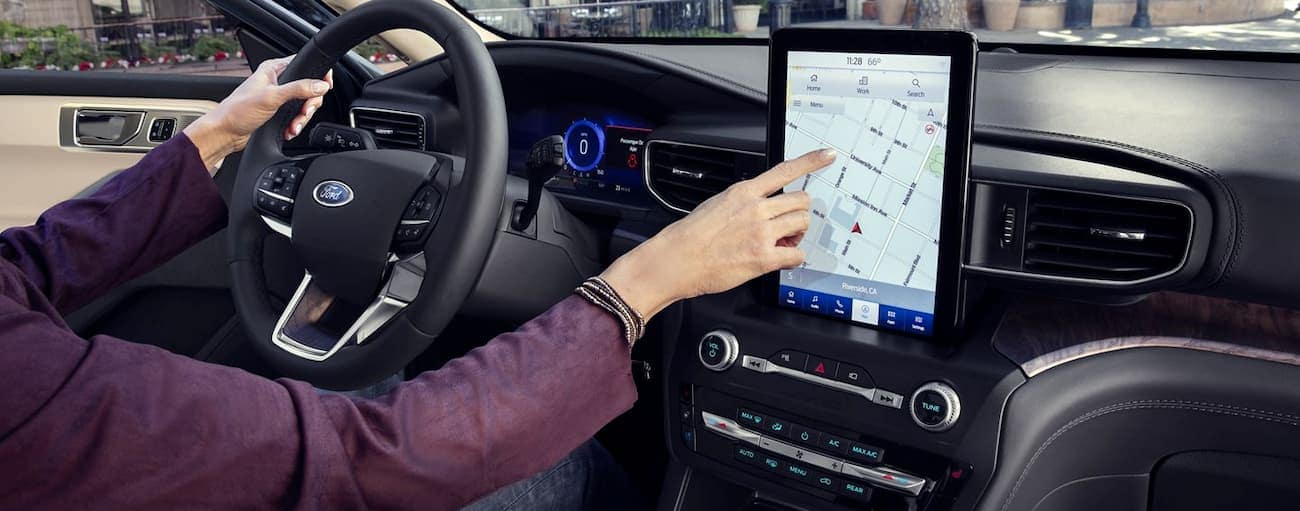 A person is using the maps feature on the touchscreen in their 2020 Ford Explorer.