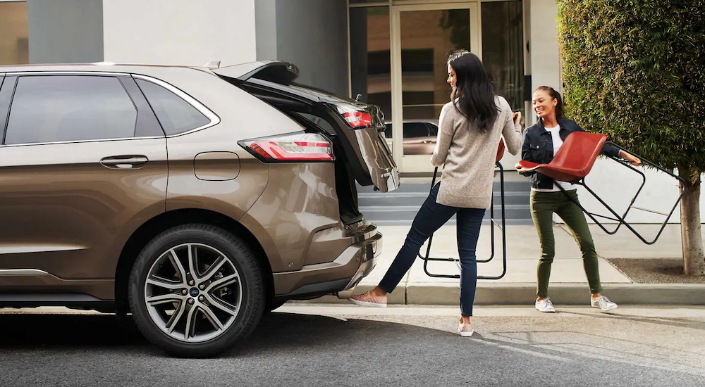 Two young women are loading chairs in the back of their tan 2019 Ford Edge that they got using Ford lease deals in Cincinnati, OH.